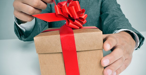 Man opening a corporate gift wrapped in a brown box with a red bow