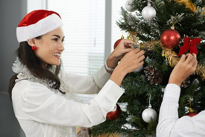 Woman decorating the christmas tree in her office