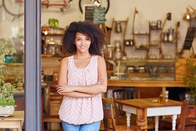 woman standing in front of small business