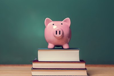 piggy bank sitting on top of textbooks