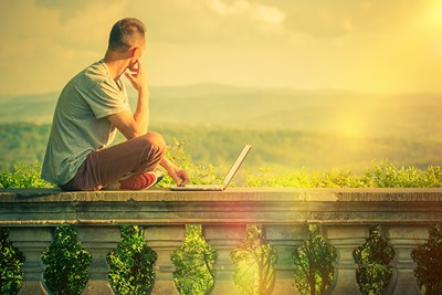 a young man sitting on a balcony with his laptop looking out over a mountainous landscape considering the idea of enrolling in an MBA entrepreneurship program