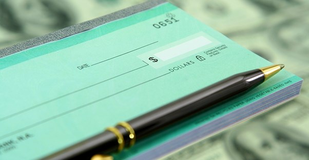 The right side of a teal green checkbook with a pen laying on top and a background of blurry dollar bills to show that a corporation is ready to use their checking account
