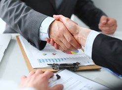 new business owner shaking hands with banker after getting business loan