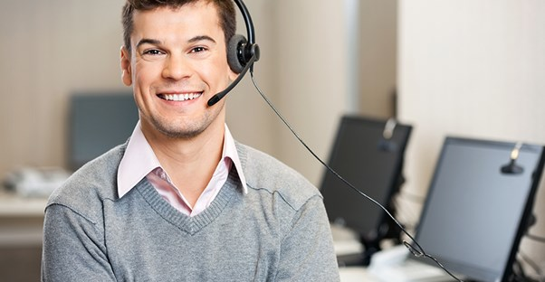 young man smiling while working in an outsourced call center