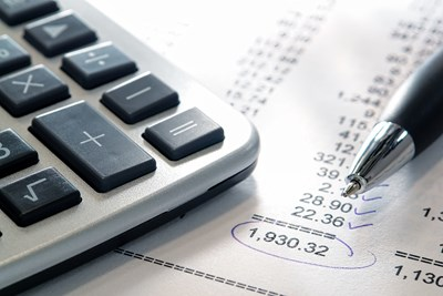 A business' financial sheet with a calculator and a pen