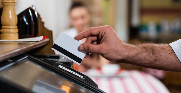Man arm swiping a credit card at a point of sale terminal