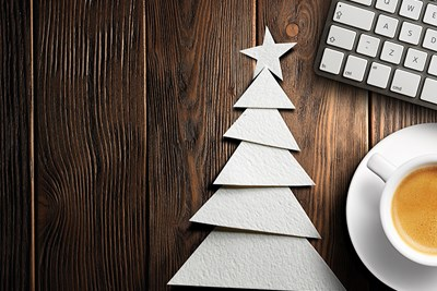 A handmade christmas tree card next to a cup of coffee and a keyboard