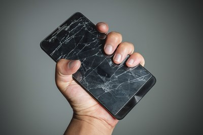 Hand clutching a phone with a shattered screen