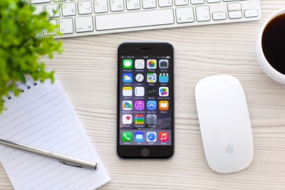 Apple iphone laying on a desk next to a magic mouse and a notebook