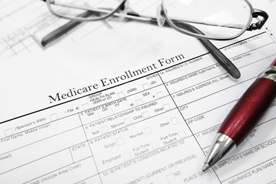 Glasses and a pen on a medicare enrollment form
