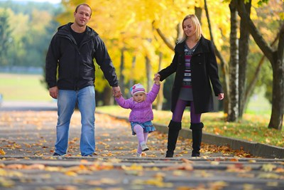 A father and mother holding their young daughters hands as they all walk down a path covered in leaves and lined with bright yellow fall trees to represent why term life insurance is important