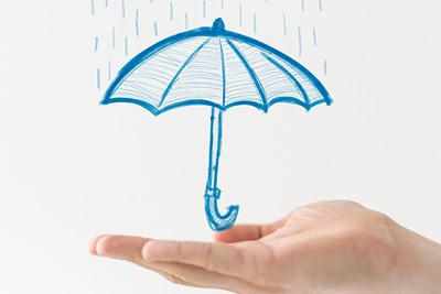 a man presenting a sketch of an umbrella to illustrate how the types of liability insurance protect comapnies