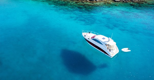 a boat covered by boat insurance on very clear blue water