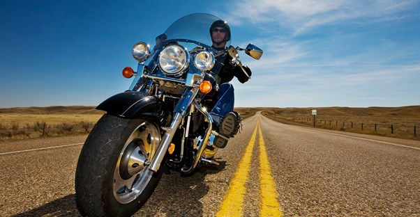 a man rides a motorcycle down a deserted 2-lane highway