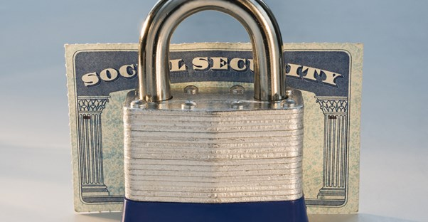 A lock standing in front of a social security card to represent the advantages and disadvantages of social security.