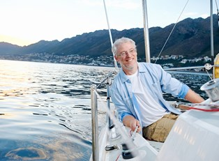 A retired gentlemen smiling on his boat because he understands the basics of social security retirement benefits.