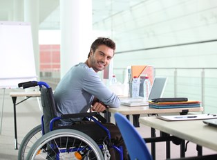 Man in a wheelchair smiling while using his laptop