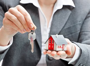 Person holding a key to a rental property covered by rental insurance