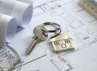 Key laying on a layout of an insured rental property