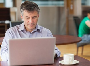 man researching IRA loans on a laptop with a cup of coffee.