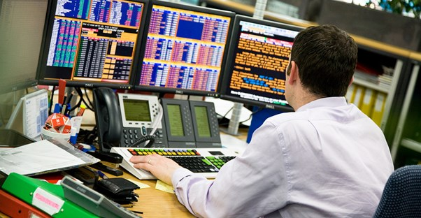 A stock analyst sits at his desk