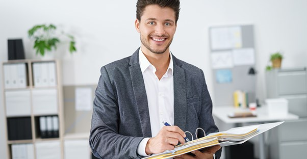 male employment lawyer in casual suit smiling and writing in binder