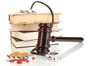 Gavel, stack of books, stethoscope, and pills.
