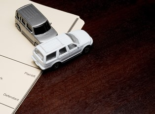 Toy cars in a collision on top of papers on a desk to represent the disadvantages of an accident injury lawyer