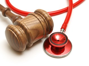 A wooden gavel and red stethoscope lying next to each other to represent the importance of using an accident injury lawyer after being injured in an accident.
