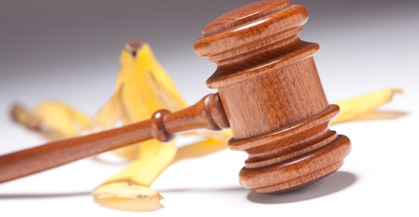 A banana peel laying on the ground behind a wooden gavel to represent how accident injury lawyers legally achieve compensation for injured individuals.