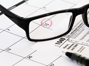 Glasses sitting on a calendar with tax day circled