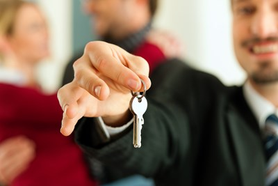 A landlord handing a new tenant the keys to their new place
