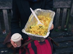 Woman holding coffee and a takeout order of fried rice