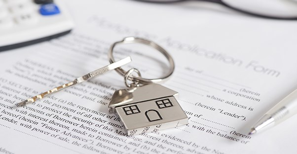 A key to a house on top of mortgage lending paperwork