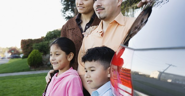 Family standing next to a minivan