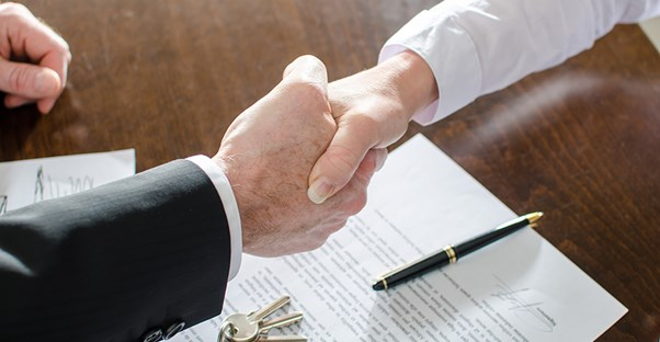 Man shaking hands as he signs a loan
