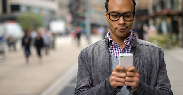 Man holding a noncontract cell phone on a busy street