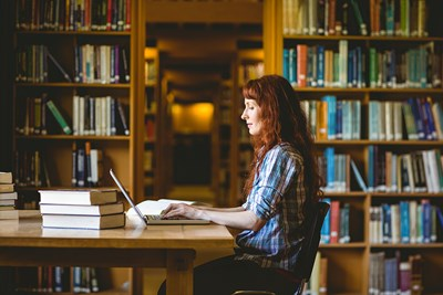 girl working on laptop inside library at community college