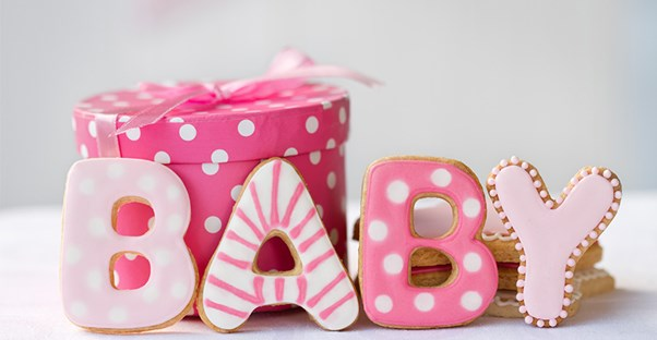 baby spelled out in pink cookies next to baby shower gift