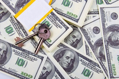lots of scattered stacks of one hundred dollar bills and a set of two keys resting on top of the stacks to show that the protection of escrow costs some money