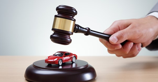A dark wood gavel in the hand of a man in a suit about to hit a sounding block with a toy red sports car on top to show that you can auction for cars