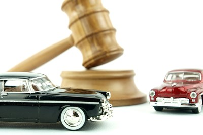 a light wood gavel resting on a sounding block with a toy red antique town car on the right side and a black version of the same toy car in front of it to show that you can bid on cars at auctions