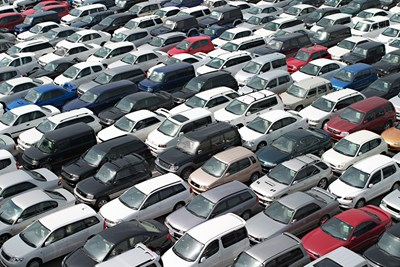 above view of cars in lines and rows prepared for a dealer car auction which is different from a public vehicle auction
