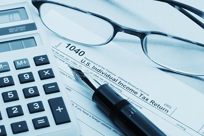 a calculator, a pair of glasses, and a pen laying on top of a 1040 income tax form where you record AGI