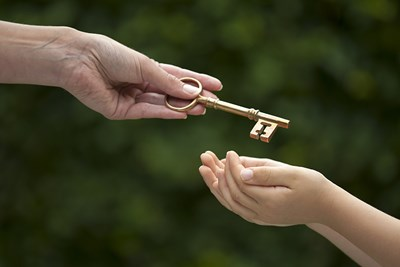 a child receiving a key to the inheritance from an adult