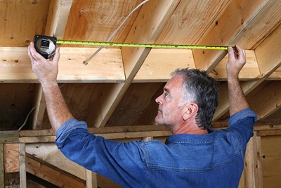 Man measuring ceiling beams. Home inspection.