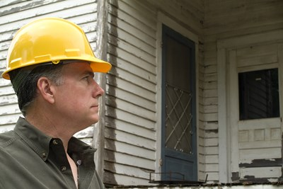 Home inspector looking at house.