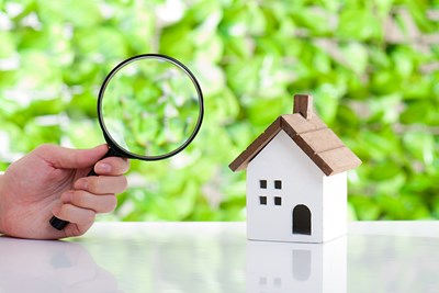 Magnifying glass looking at a toy house. Home inspections.