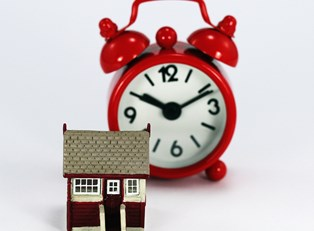 Small house sitting next to an alarm clock to represent good timing for home refinancing