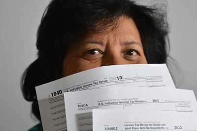 a woman holds tax filing forms in front of her face so only her eyes are showing